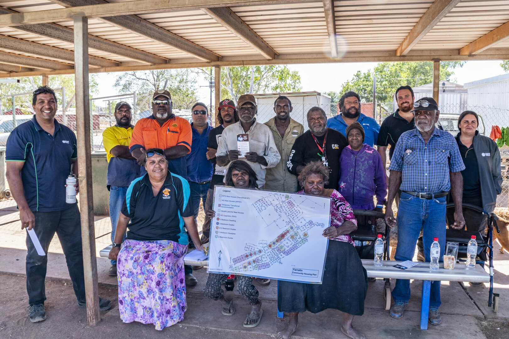 Aboriginal community members and government workers stand under a patio, holding a map of their community